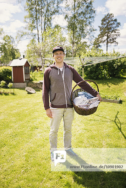 Schweden  Vasterbotten  Lächelnder Mann mit Wäschekorb auf Rasen stehend