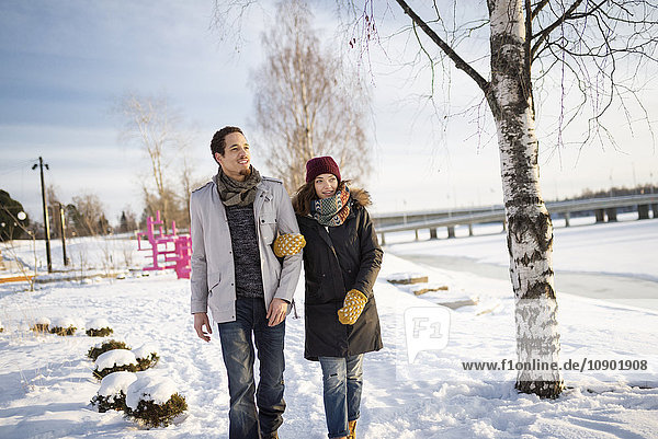 Sweden,  Vasterbotten,  Umea,  Young couple walking in snow by river