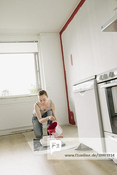 Schweden  Frau gießt Farbe in die Farbwanne in der Küche