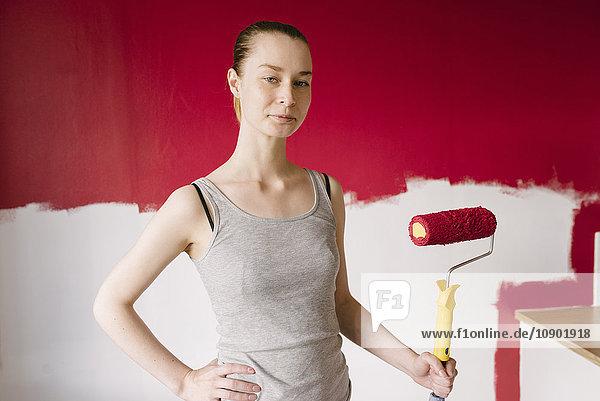 Schweden  Porträt einer Frau mit Farbroller an der Wand