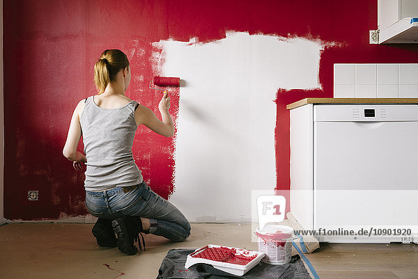 Sweden,  Woman painting wall in kitchen