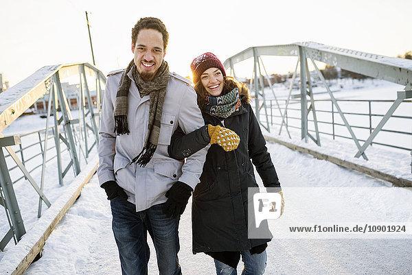 Schweden  Vasterbotten  Umea  Junges Paar auf der Fußgängerbrücke im Winter