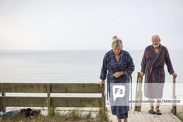 Schweden  Skane  Ahus  Seniorenpaar im Bademantel vom Strand zurückkommend