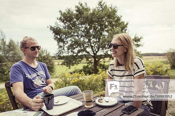 Schweden  Skane  Ostra Goinge  Paar bei Tisch entspannen
