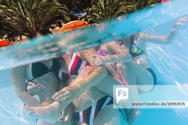 Italien  Sardinien  Alghero  Mutter mit Kindern (14-15  16-17) umarmend am Schwimmbad