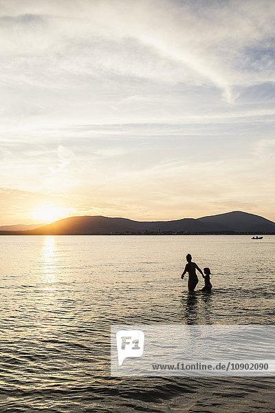 Italien  Sardinien  Alghero  Mutter und Tochter waten im Meer bei Sonnenuntergang