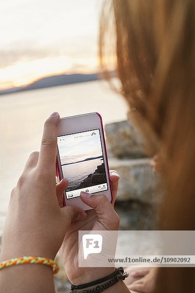 Italien  Sardinien  Alghero  Teenage Girl (16-17) fotografiert das Meer bei Sonnenuntergang mit einem Smartphone.