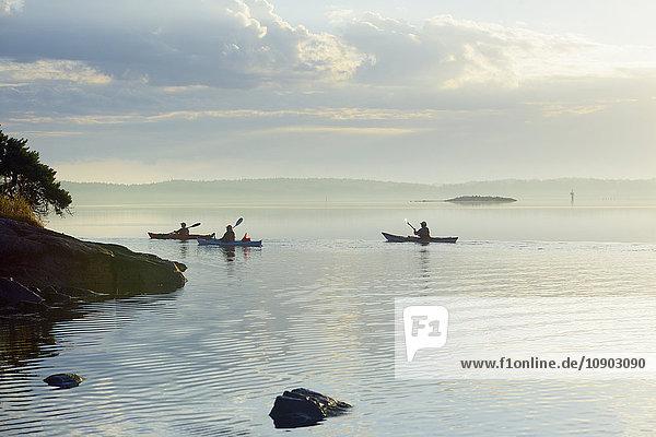 Schweden  Uppland  Stockholm Archipel  Lidingo  Gashaga  Hustegafjarden  Drei Personen Kajakfahren im ruhigen Meer rund um die Felsvorsprünge