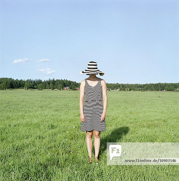 Finnland  Uusimaa  Lapinjarvi  Junge Frau mit Hut auf Gras stehend