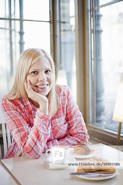 Finnland  Helsinki  Esplanadi  Frau am Tisch sitzend mit einer Tasse Kaffee  lächelnd
