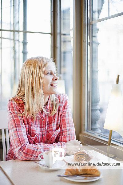Finnland  Helsinki  Esplanadi  Frau schaut durchs Caféfenster  lächelnd