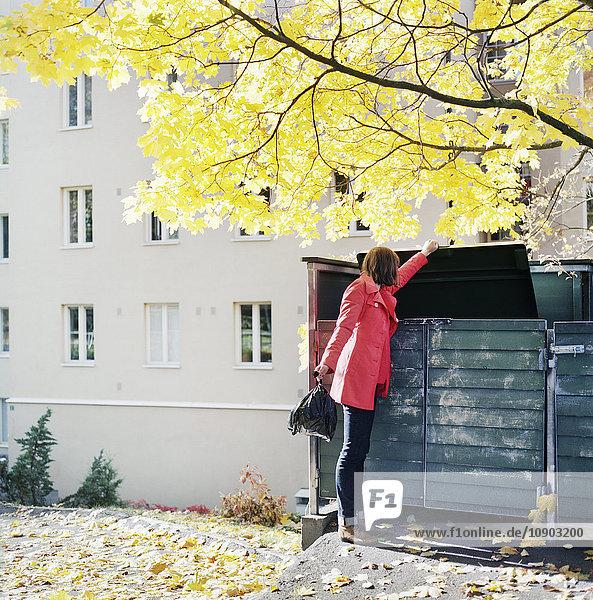 Finnland  Helsinki  Kallio  Frau wirft Müllsack in Mülltonne