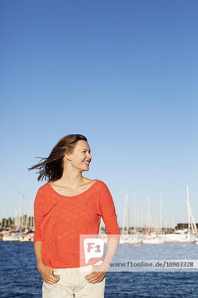 Finnland  Uusimaa  Helsinki  Kaivopuisto  Portrait der lächelnden jungen Frau mit Meer im Hintergrund