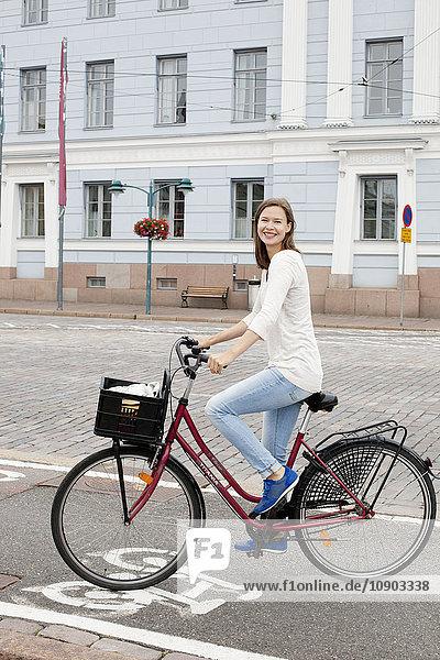 Finland  Uusimaa  Helsinki  Kruunuhaka  Young woman riding bicycle in city