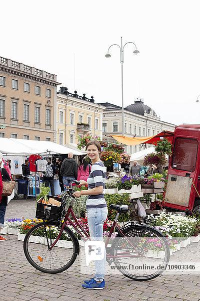Finnland  Uusimaa  Helsinki  Kauppatori  Portrait einer lächelnden jungen Frau mit Fahrrad auf dem Straßenmarkt
