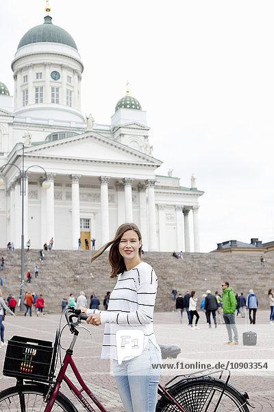 Finnland  Uusimaa  Helsinki  Senaatintori  Junge Frau mit Fahrrad mit lutherischer Kathedrale im Hintergrund