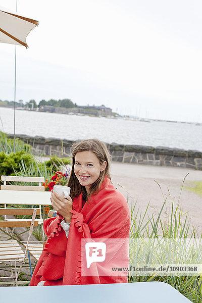 Finnland  Uusimaa  Helsinki  Kaivopuisto  Porträt einer lächelnden jungen Frau beim Trinken von Heißgetränken