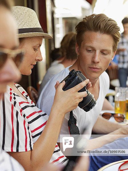 Frankreich  Paris  Touristen sitzend im Side Walk Cafe mit Kamera