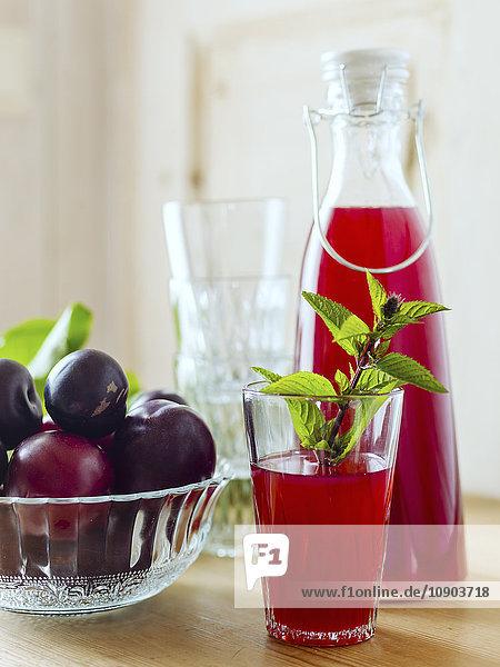 Schweden  Karaffe und Glas mit Pflaumensaft und Schale voller Pflaumen