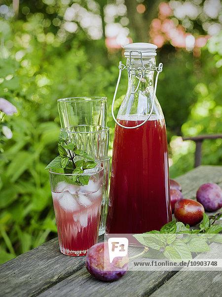 Schweden  Pflaumensaft in Glas und Karaffe  Pflaumen und Glasstapel auf dem Tisch