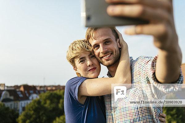 Deutschland  Berlin  Junges Paar umarmt und nimmt Selfie mit Smartphone