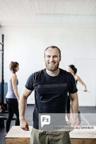 Deutschland  Junge Männer und Frauen stehen im Fitnessstudio