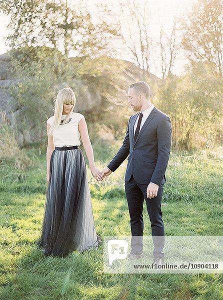 Schweden  Brautpaar auf Rasen stehend  Händchen haltend