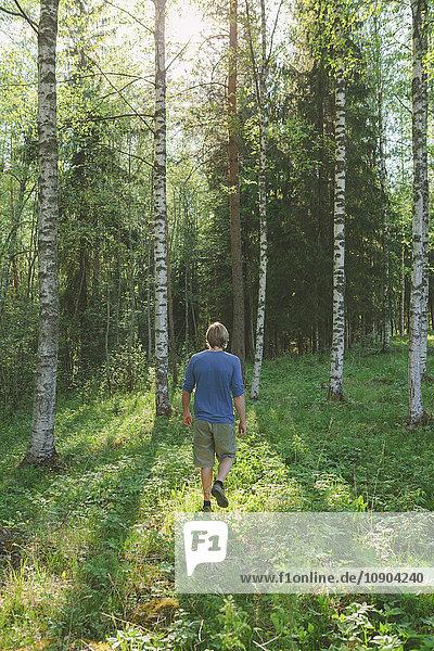 Finnland  Mellersta Finnland  Jyvaskyla  Saakoski  Junger Mann auf der Waldwiese