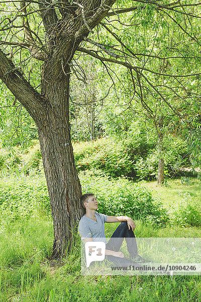 Finnland  Helsinki  Aggelby  Junger Mann unter trockenem Baum sitzend