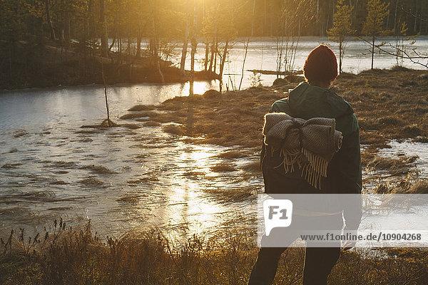 Finnland  Esbo  Kvarntrask  Junger Mann steht am sumpfigen Seeufer