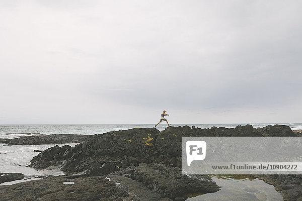 USA  Hawaii  Big Island  Mann springt über eine Felsspalte am Meer