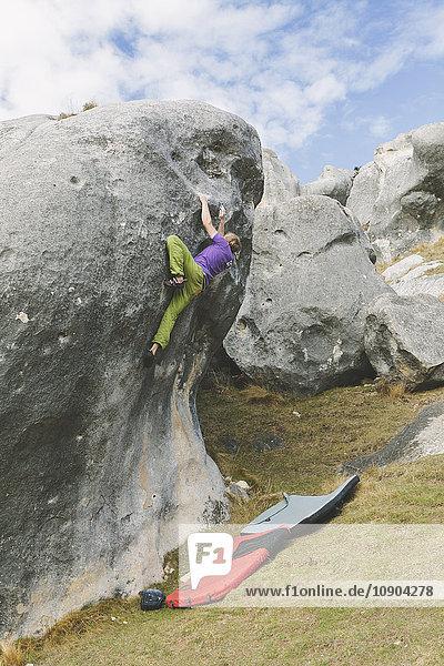 Neuseeland  Castle Hill  Junger Mann klettert auf Felsbrocken mit zwei Crashpads darunter