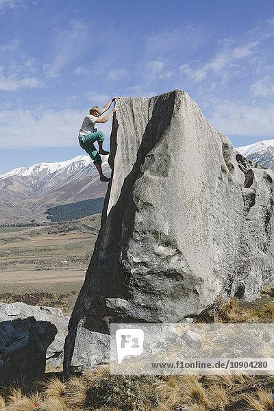 Neuseeland  Castle Hill  Junger Mann klettert steile Felswand hinauf