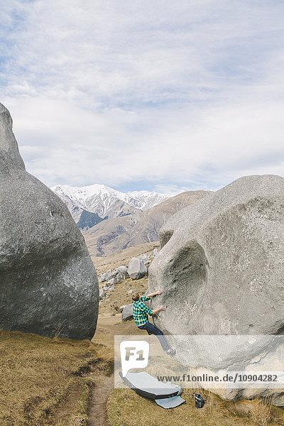 Neuseeland  Castle Hill  Junger Mann klettert auf Felsen mit schneebedeckten Bergen in der Ferne.