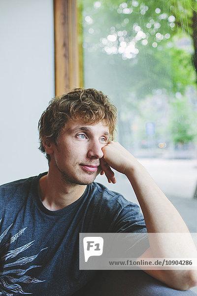 Finnland  Mann im mittleren Erwachsenenalter schaut durchs Fenster