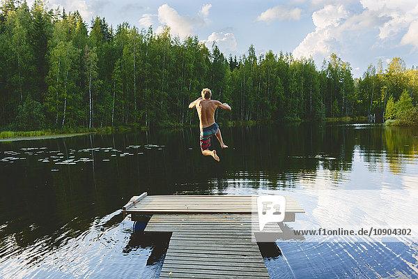 Finnland  Keski-Suomi  Jyvaskyla  Vuohijarvi-See  Junger Mann springt vom Pier in den See