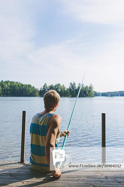 Finnland  Pirkanmaa  Salmentaka  Palkanevesi-See  Junger Mann beim Angeln vor der Seebrücke