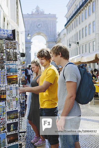 Portugal  Lissabon  Drei Touristen wählen Postkarten