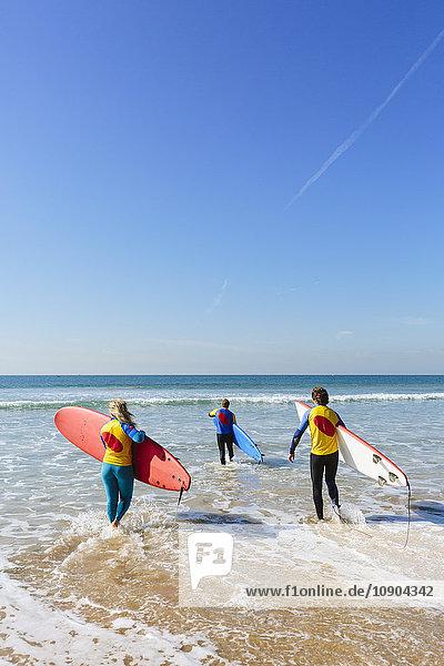 Portugal  Lissabon  Drei Personen mit Surfbrettern