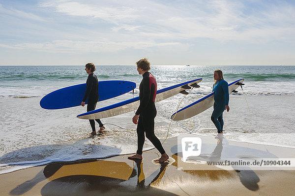 Portugal  Lissabon  Drei Personen mit Surfbrettern am Strand