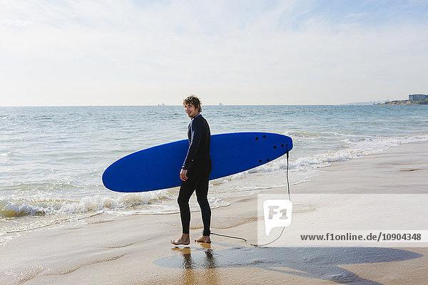 Portugal  Lissabon  Mann mit Surfbrett am Strand