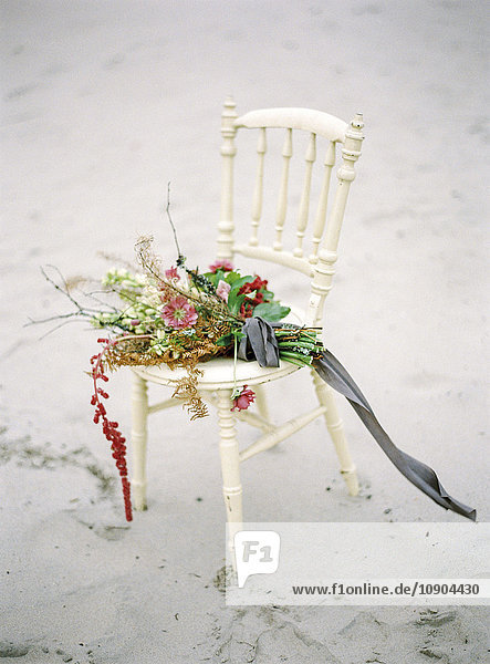 Schweden  Blumenstrauß auf altmodischem Stuhl am Sandstrand