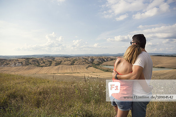 Italy  Tuscany  Hugging couple looking at field landscape