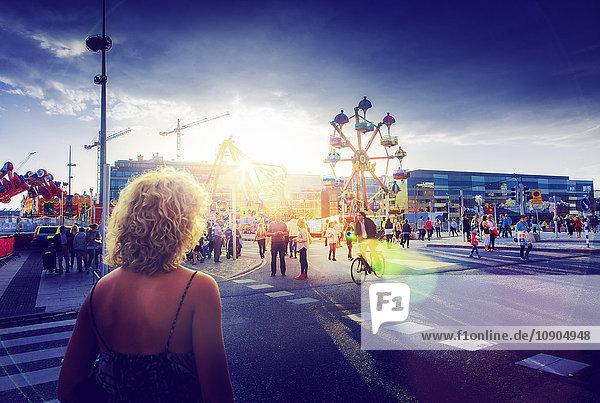 Schweden  Skane  Malmö  Anna Lindhs Plats  Frau überquert Stadtstraße in Richtung Karnevalsgelände