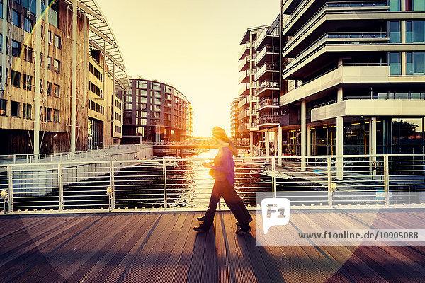 Norwegen  Oslo  Aker Brygge  Fußgänger auf der Stadtbrücke im Schatten der untergehenden Sonne