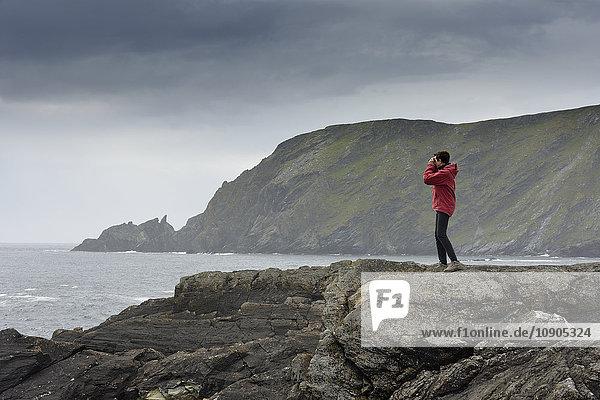 UK  Schottland  Shetland  Garth´s Ness  Seniorin auf dem Felsen stehend  mit Blick auf die Aussicht