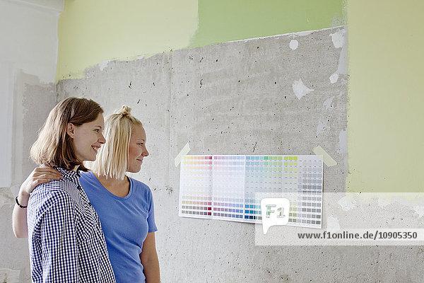 Finnland,  Junge Frauen beim Betrachten von Farbmustern an der Wand, Finnland,  Junge Frauen beim Betrachten von Farbmustern an der Wand