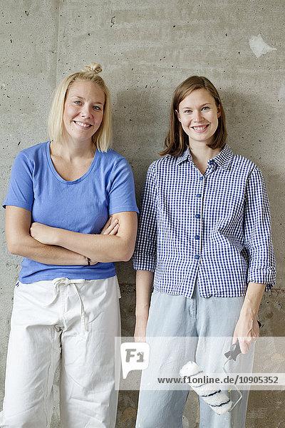 Finnland  Junge Frauen stehen an der Wand und halten Farbroller