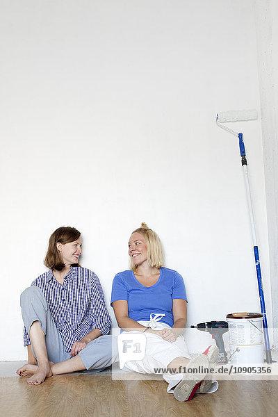 Finnland  Junge Frauen  die sich nach der Renovierung des Hauses an der Wand ausruhen
