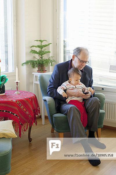 Finnland  älterer Mann sitzt im Sessel und hält Enkel (18-23 Monate) auf Runden.